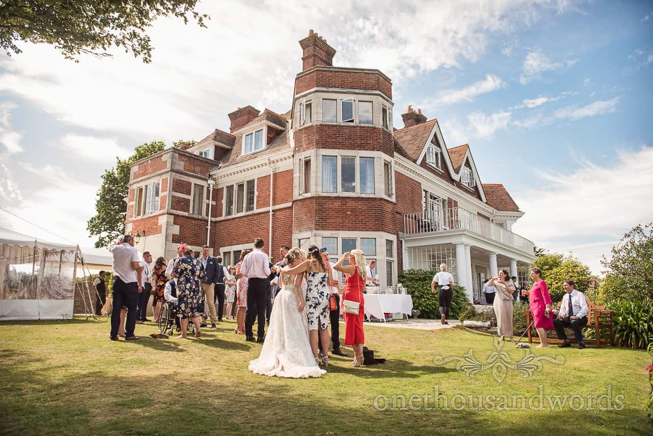 Bride hugged by wedding guest at garden drinks reception at Studland Bay Dorset wedding photograph