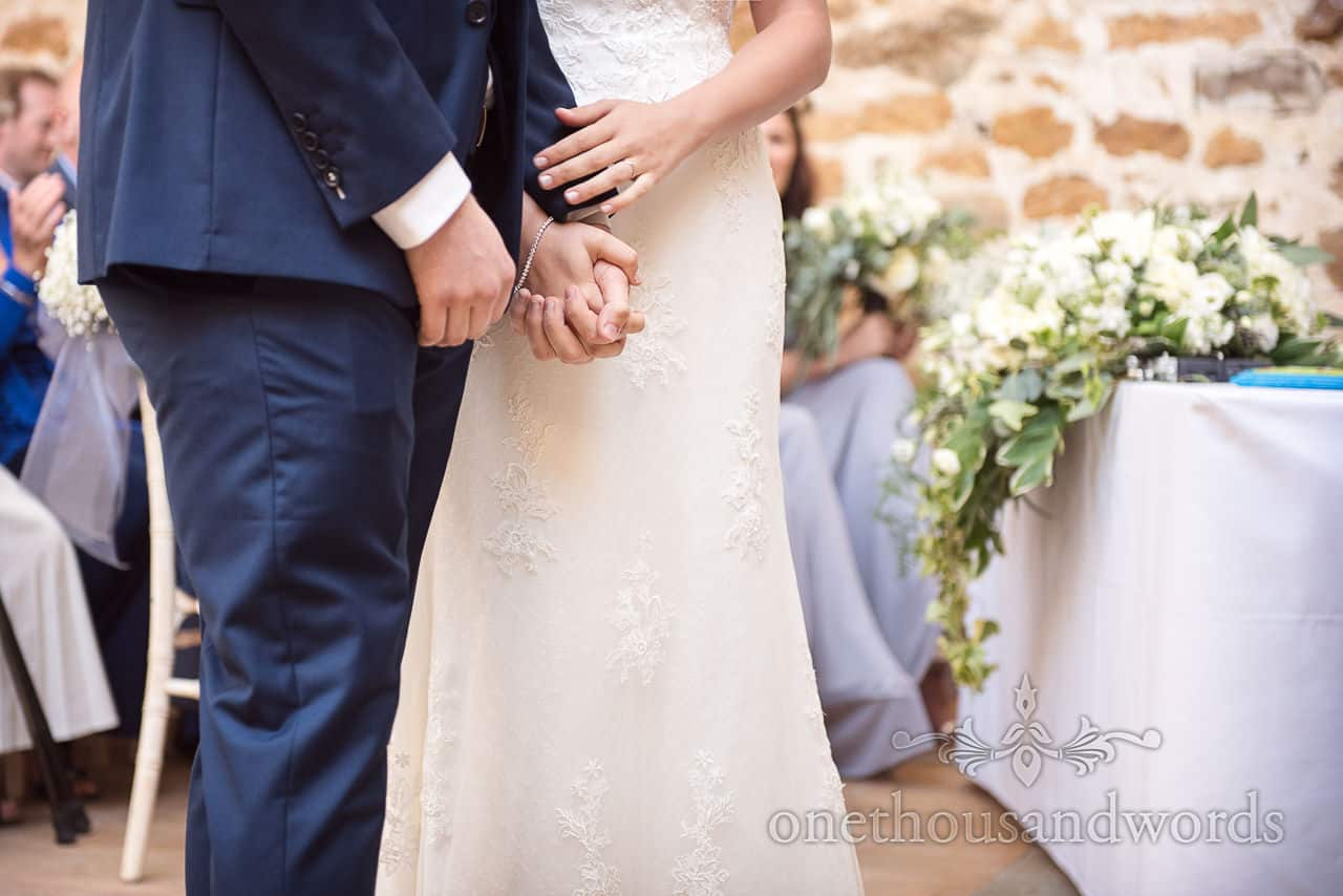 Bride and groom in blue wedding suit holding hands during civil ceremony at the Tithe Barn Dorset wedding venue