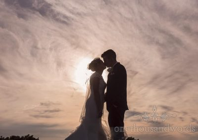 Bride and groom kissing silhouette against sun and swirling clouds from Golf club wedding reception