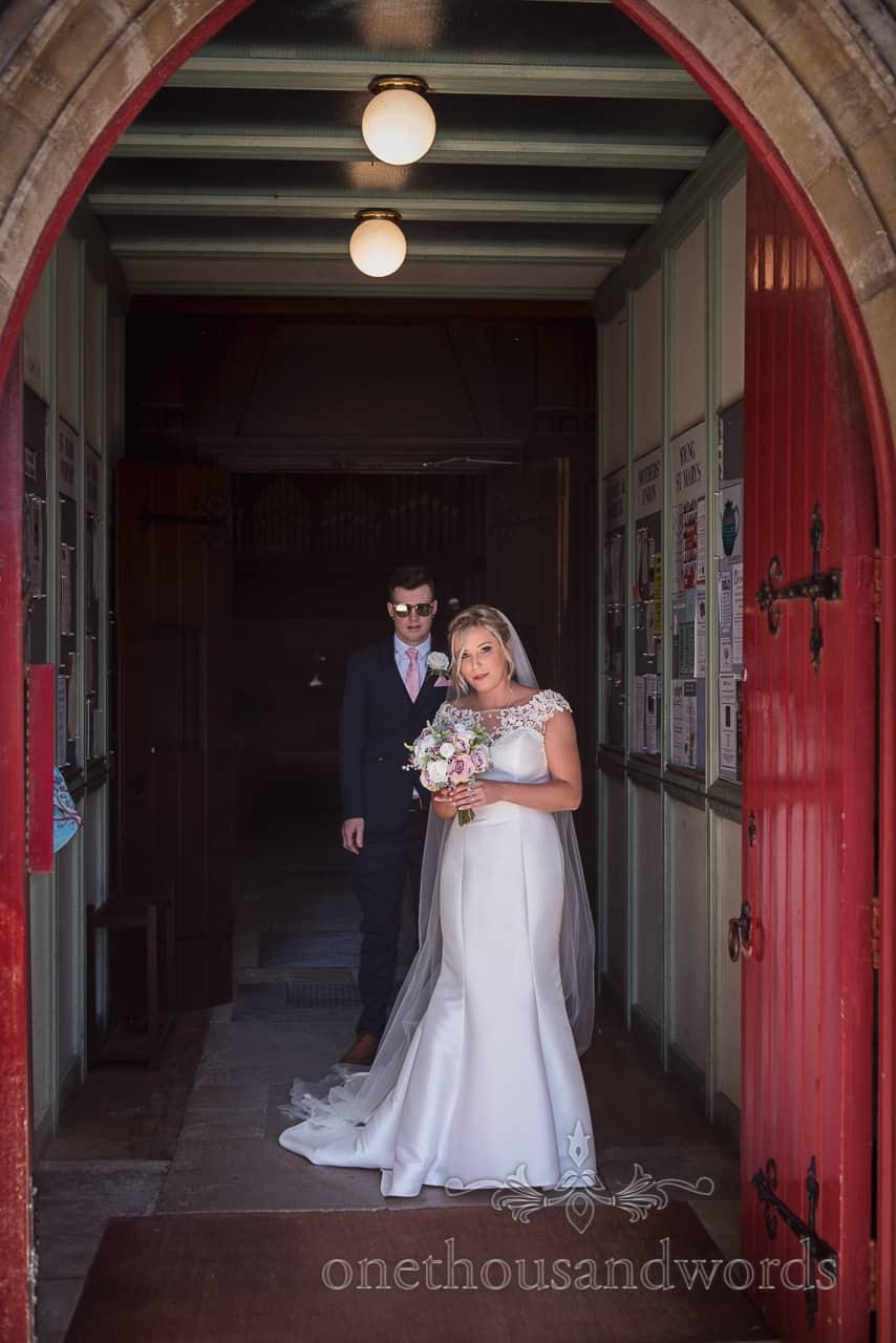 Bride and groom shelter hot sun in Dorset church doorway in Swanage