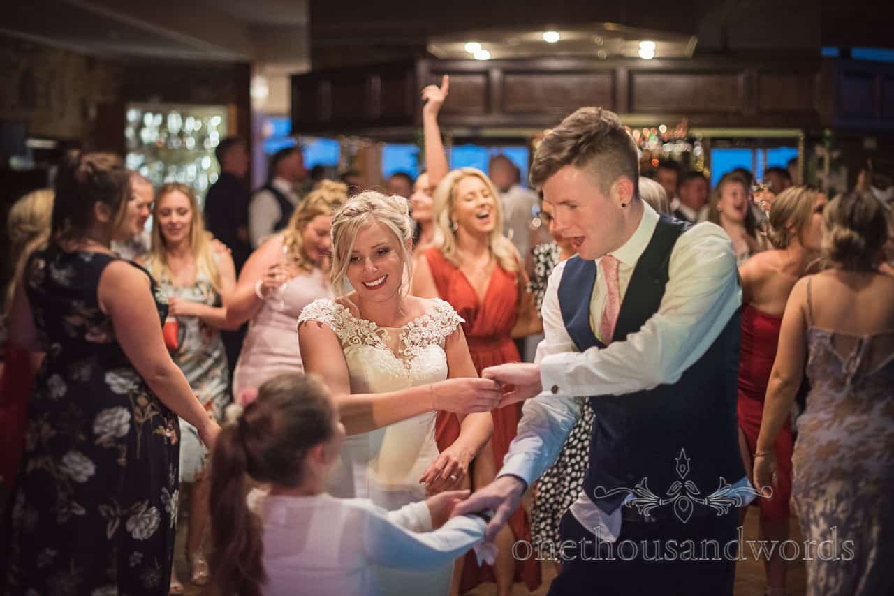 Bride and groom sing and dance with flower girl at wedding evening reception at Purbeck Golf Club