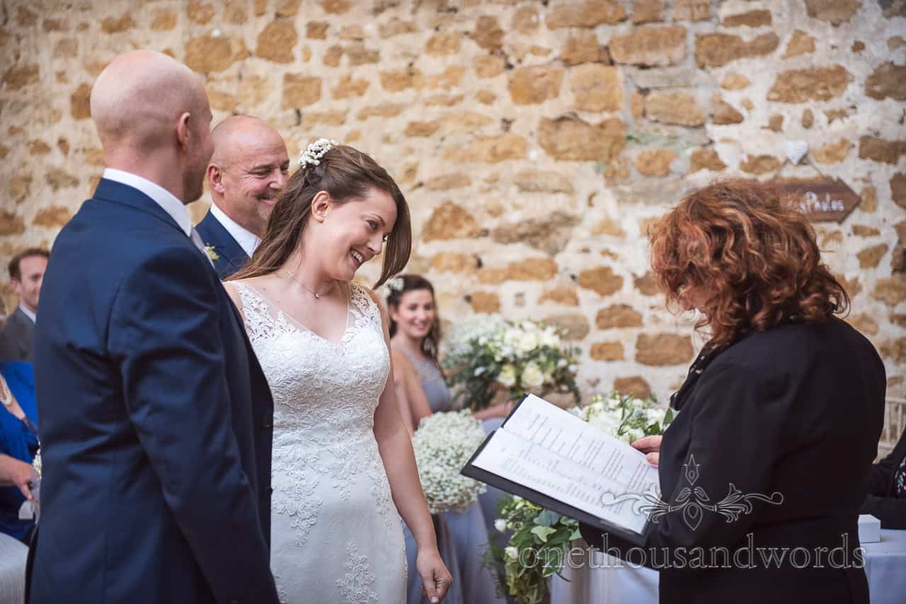 Smiling bride during civil ceremony at the Tithe Barn on the Symondsbury Estate Dorset