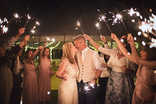 Bride and groom kiss with sparklers at end day with no limits on photographic coverage