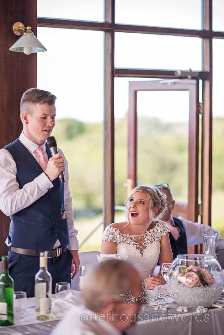 Bride laughs during groom making wedding speech at top table from Golf Club reception