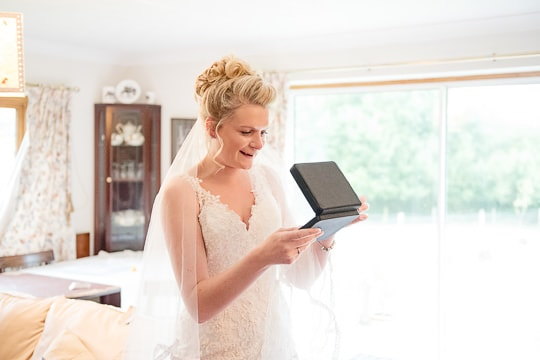 Bride photographed on wedding morning at the same time as groom preparations