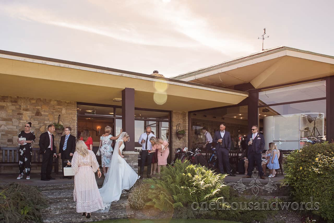 Bride shows off her wedding shoes in sunshine at Purbeck Golf Club documentary wedding photography