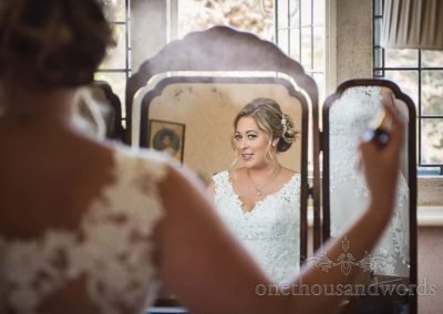 Happy bride in white wedding dress sprays perfume in ornate wooden framed mirror on wedding morning