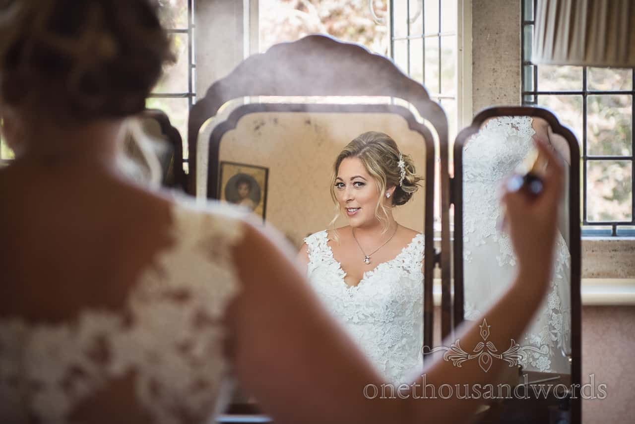 Happy bride in white wedding dress sprays perfume in ornate wooden framed mirror