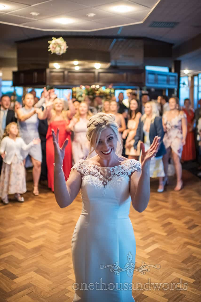Bride throws her wedding bouquet across dance floor at Purbeck Golf club reception