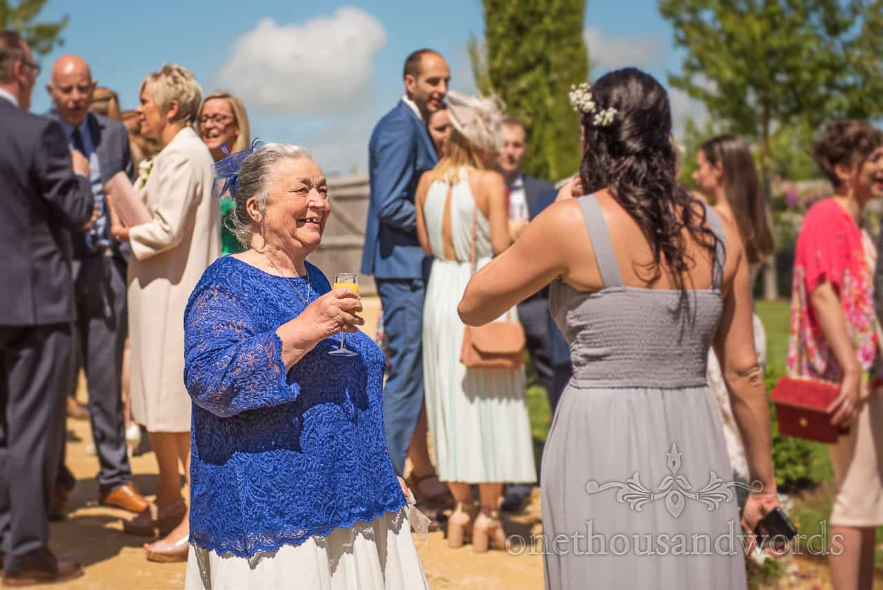 Brides grandmother wearing blue laughing with drink in hand during garden wedding drinks reception
