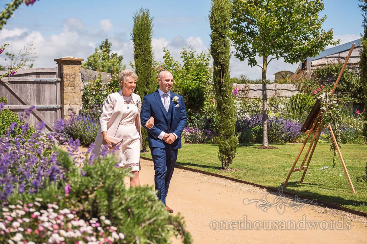 Brides mother is escorted to civil ceremony at the Tithe Barn Dorset wedding by groomsman in blue wedding suit