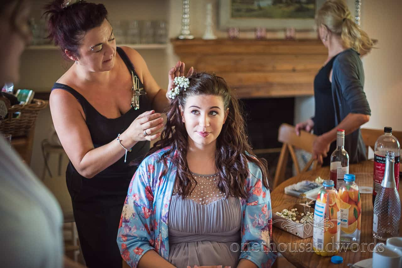 Bridesmaid in floral dressing gown has flowers worked into hair style on Dorset wedding morning