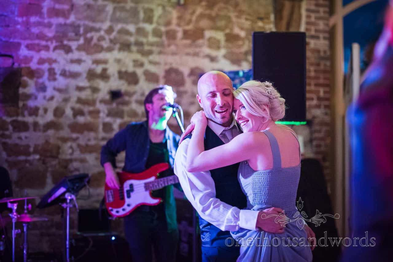 Bridesmaid and grooms man dance to the wedding band under purple disco lighting with guitarist in the background