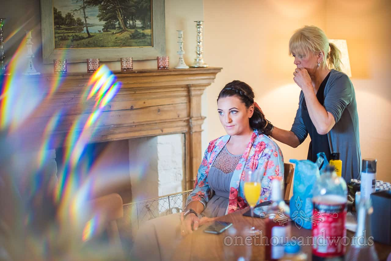 Bridesmaid in floral dressing gown has hair styled on morning of Dorset barn wedding on Symondsbury Estate