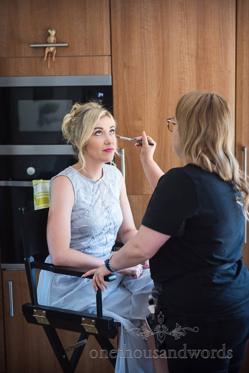 Bridesmaid in pastel Blue dress sits while having wedding makeup styled before Dorset church wedding
