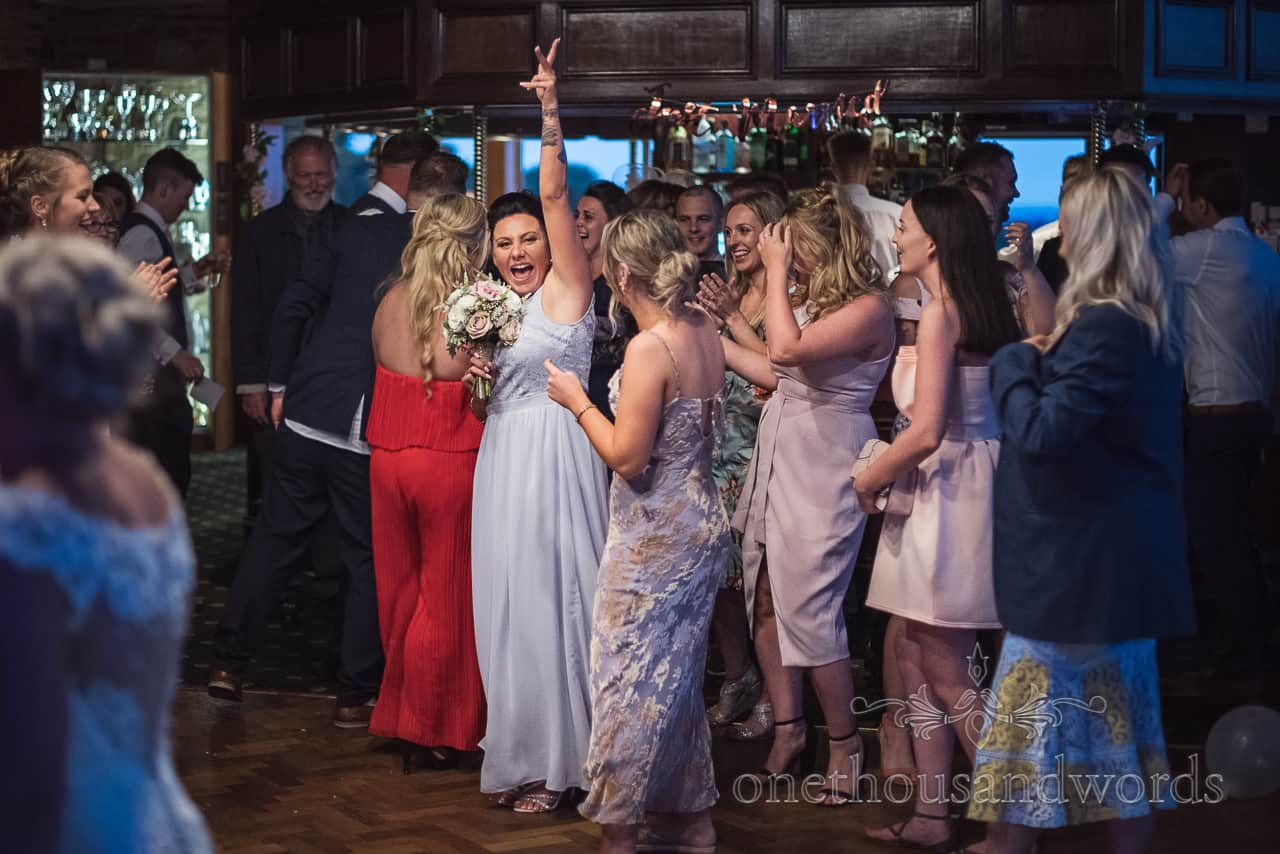 Bridesmaid in pastel blue dress excited about catching wedding bouquet at Golf Club reception in Dorset