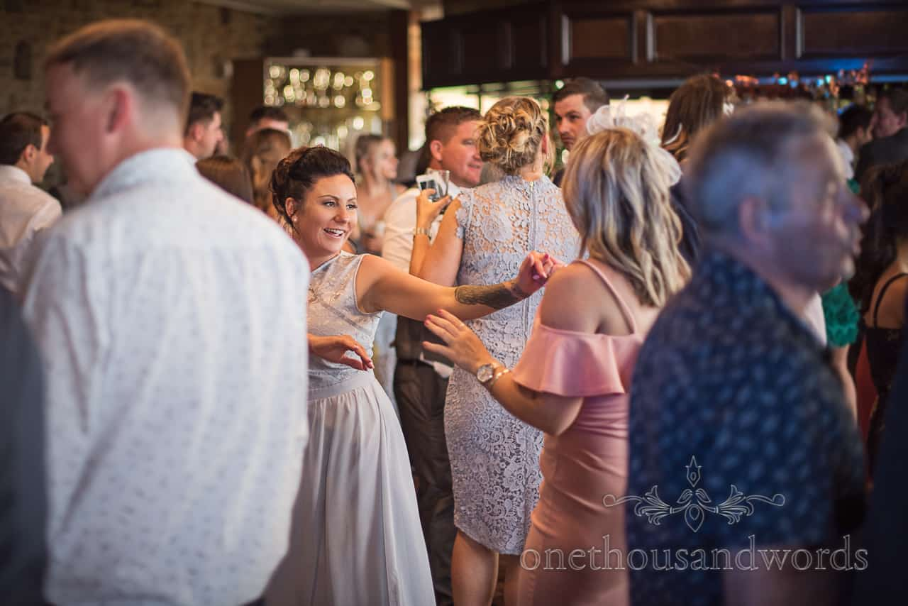 Bridesmaid in pastel Blue dress and sleeve tattoo on wedding dance floor at Golf Club reception