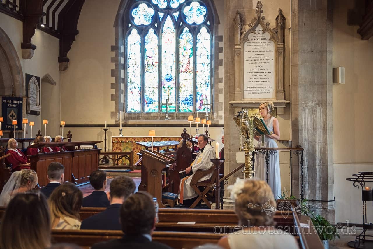 Bridesmaid in pastel Blue dress delivers reading at St Marys church Swanage wedding ceremony