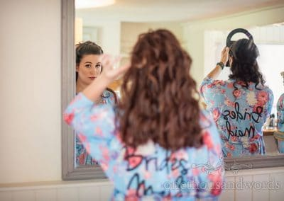 Bridesmaids in floral dressing gowns checking in mirror during morning preparations for Barn Dorset wedding