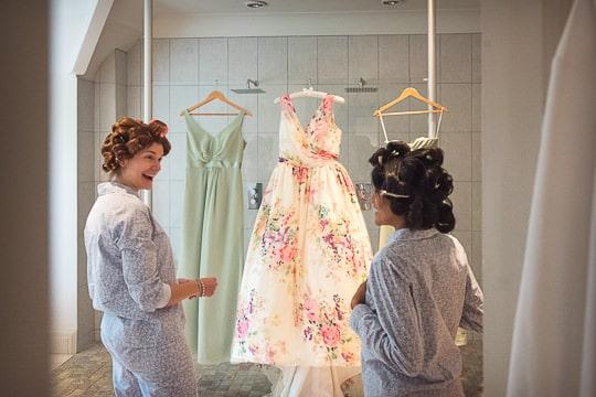 Bridesmaids examine designer wedding dress hanging on wedding morning in Dorset