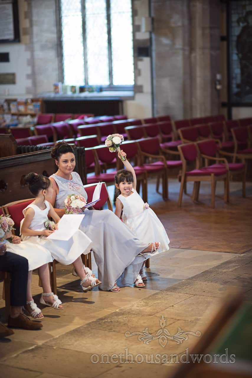 Cheeky flower girl sticks tongue out Dorset during church ceremony