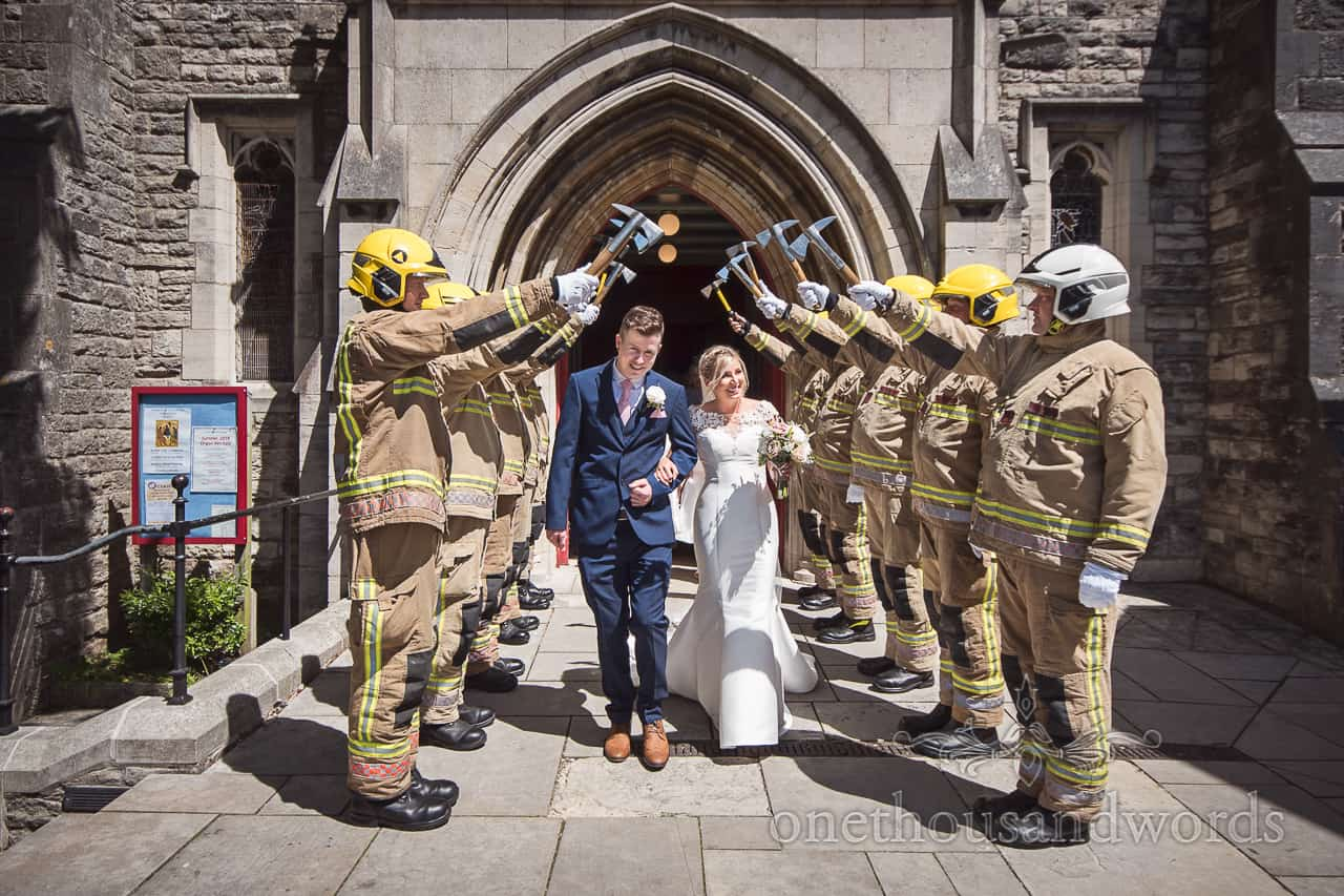 Church wedding exit guard of honour from fire men in protective clothing and helmets in Swanage