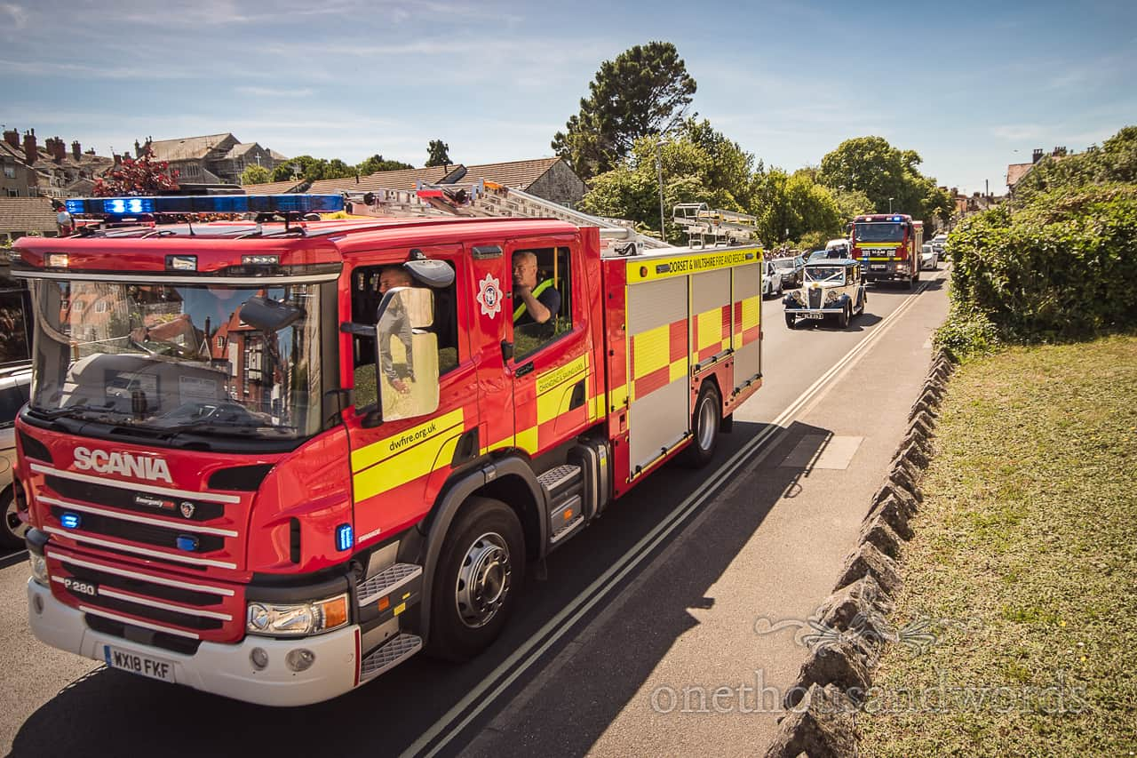 Classic wedding car transport with fire engine crew escort and blue lights in Swanage