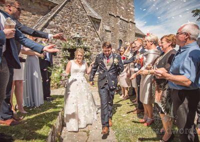 Wedding confetti photograph outside ancient Dorset stone village church on summers day