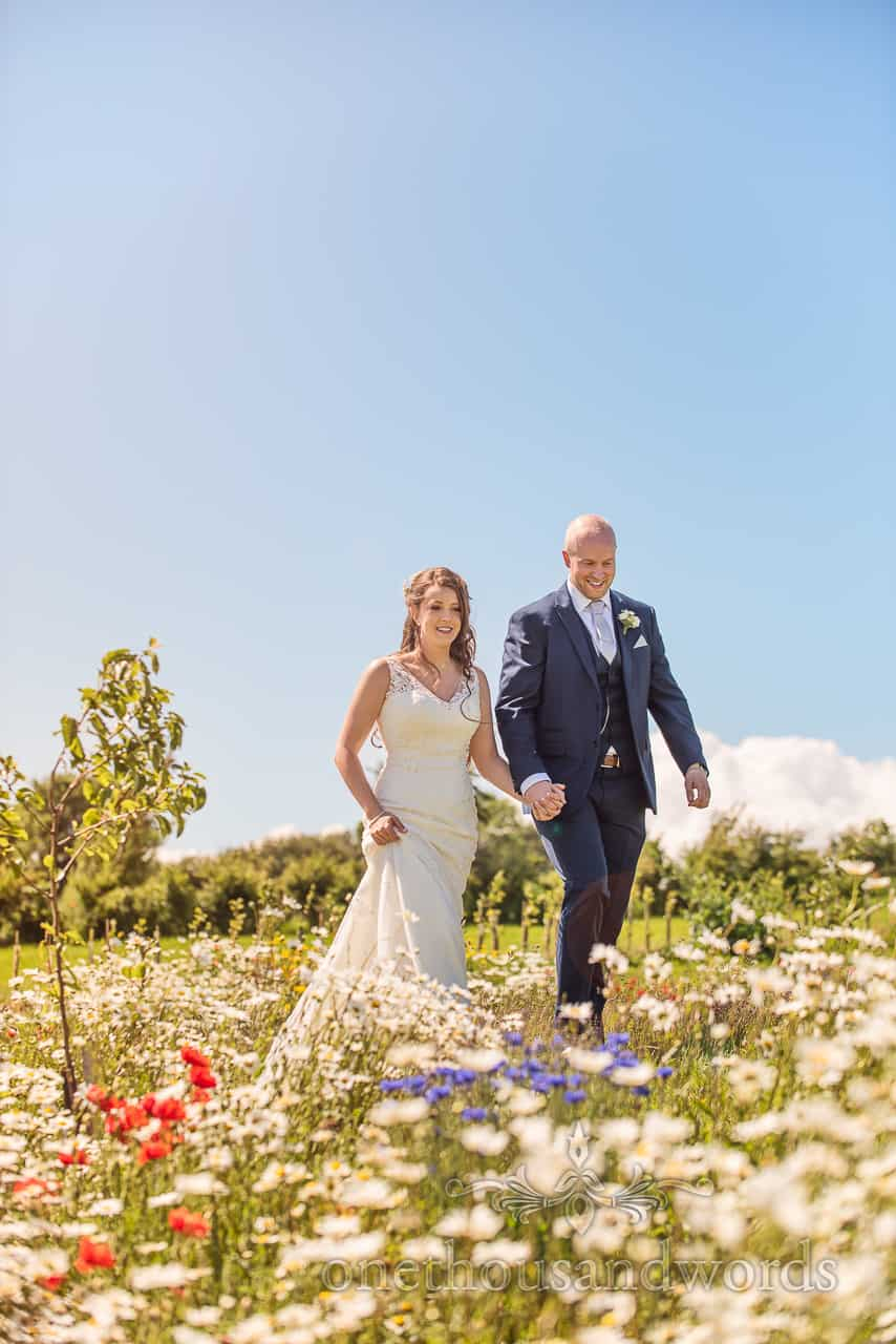 Smiling couple photograph walking in meadow of wild flowers at Tithe Barn Dorset wedding