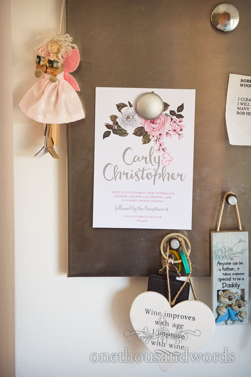 Custom wedding stationary invite hanging on magnet board with fairy and love heart