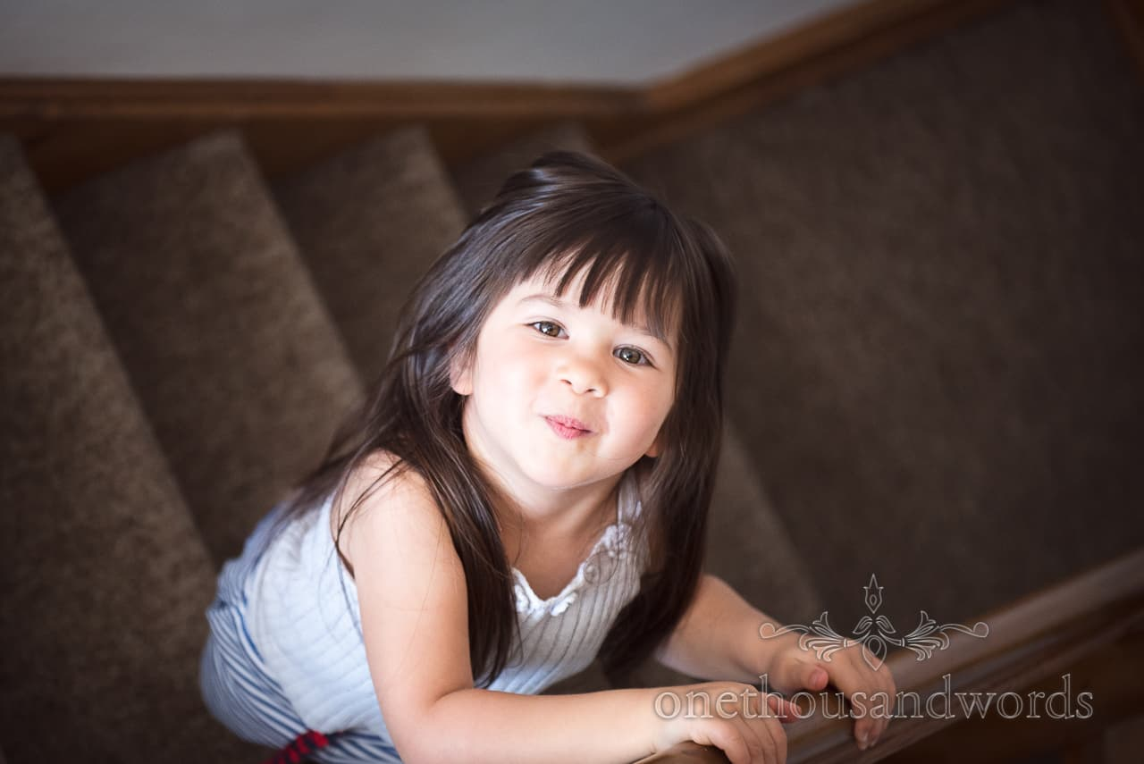 Cute cheeky flower girl playing on stairs during wedding morning documentary photographs