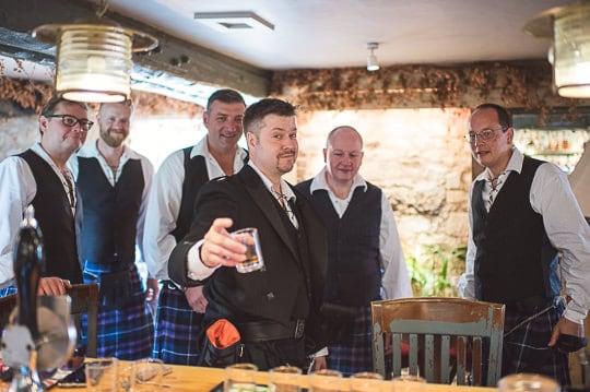 Kilted groom and groomsmen in pub on wedding morning