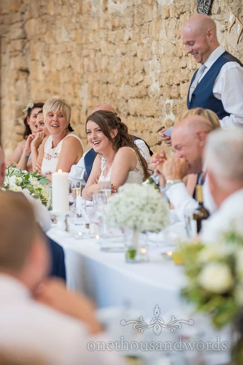 Documentary wedding photo of bride laughing at top table wedding speeches in stone barn wedding breakfast
