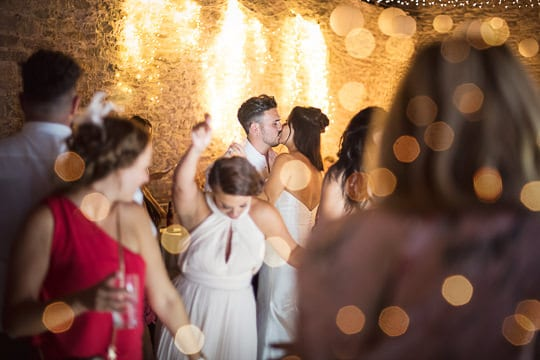 Bride and groom kiss on dance floor after twelve hour wedding day photograph by wedding photographers with no time limits