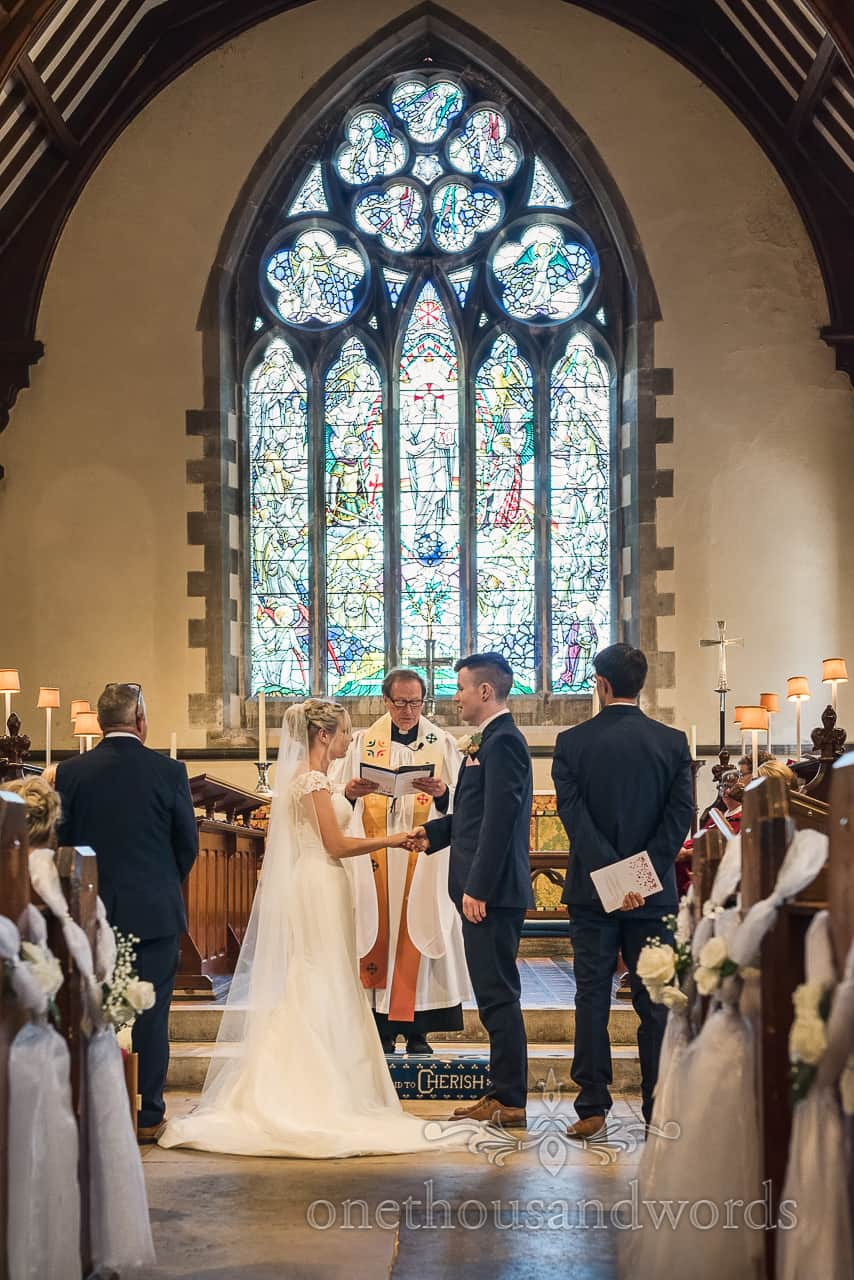 Exchange wedding rings in front of stained glass window at Dorset church wedding ceremony