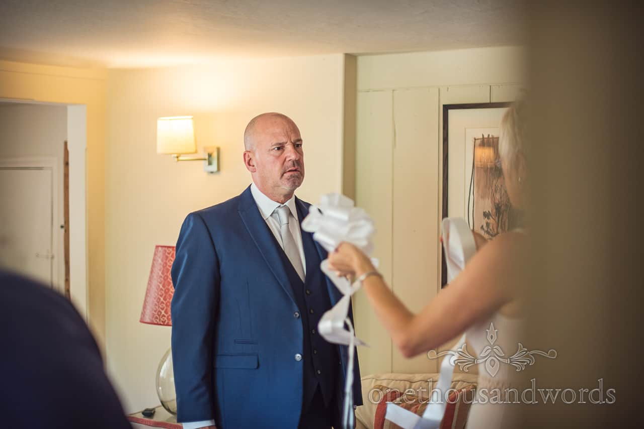 Father of the Bride in blue wedding suit pulls funny disgust face when asked to tie ribbons onto wedding car on wedding morning