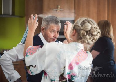 Bride styles fathers hair with hair spray during wedding morning preparations