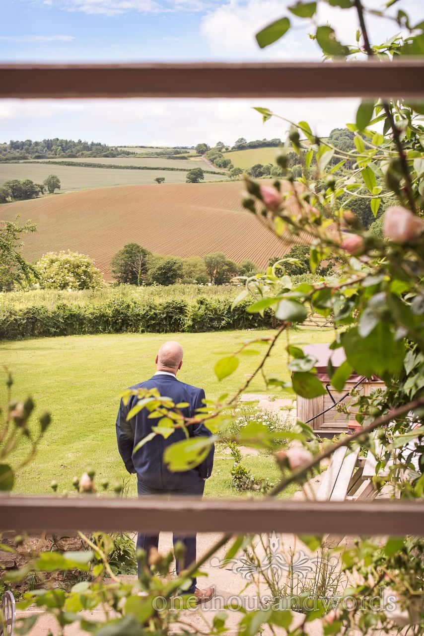 Father of the bride takes a moment to look at the Dorset countryside views at Symondsbury Estate cottage on wedding morning