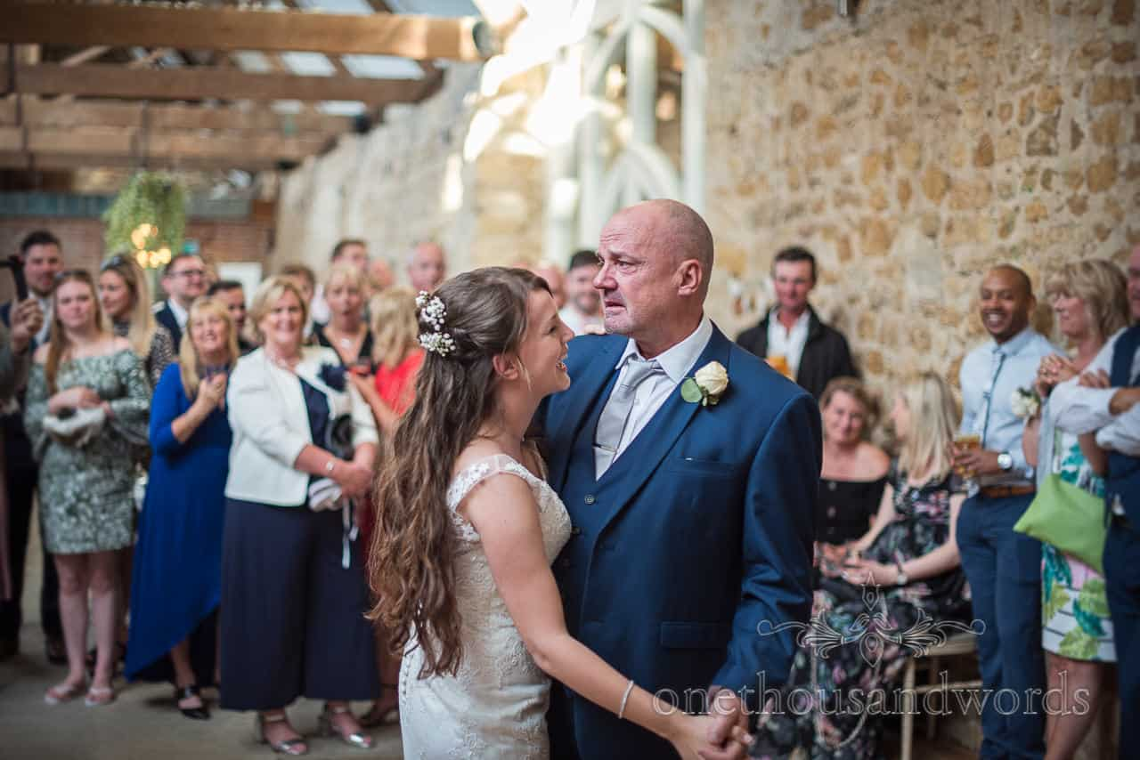 Bride laughs during father and daughter dance with emotional crying father at Tithe Barn Dorset wedding venue