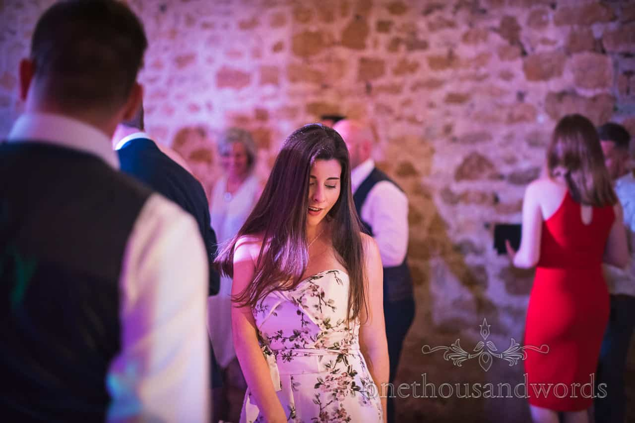 Beautiful female wedding guest in floral dress dancing and flossing on wedding evening dance floor photograph