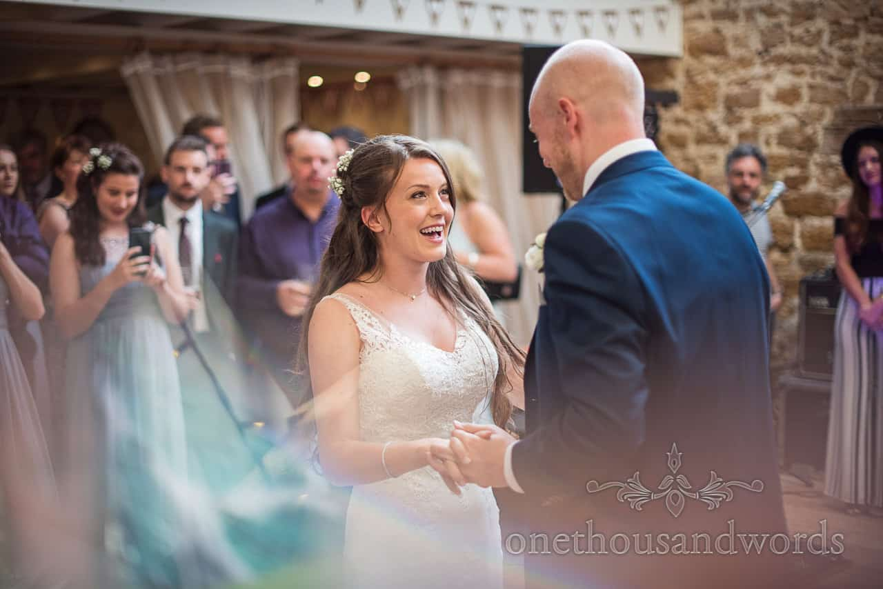Bride laughs at groom during first dance wedding photograph with lens distortion taken at Tithe Barn wedding venue in Dorset