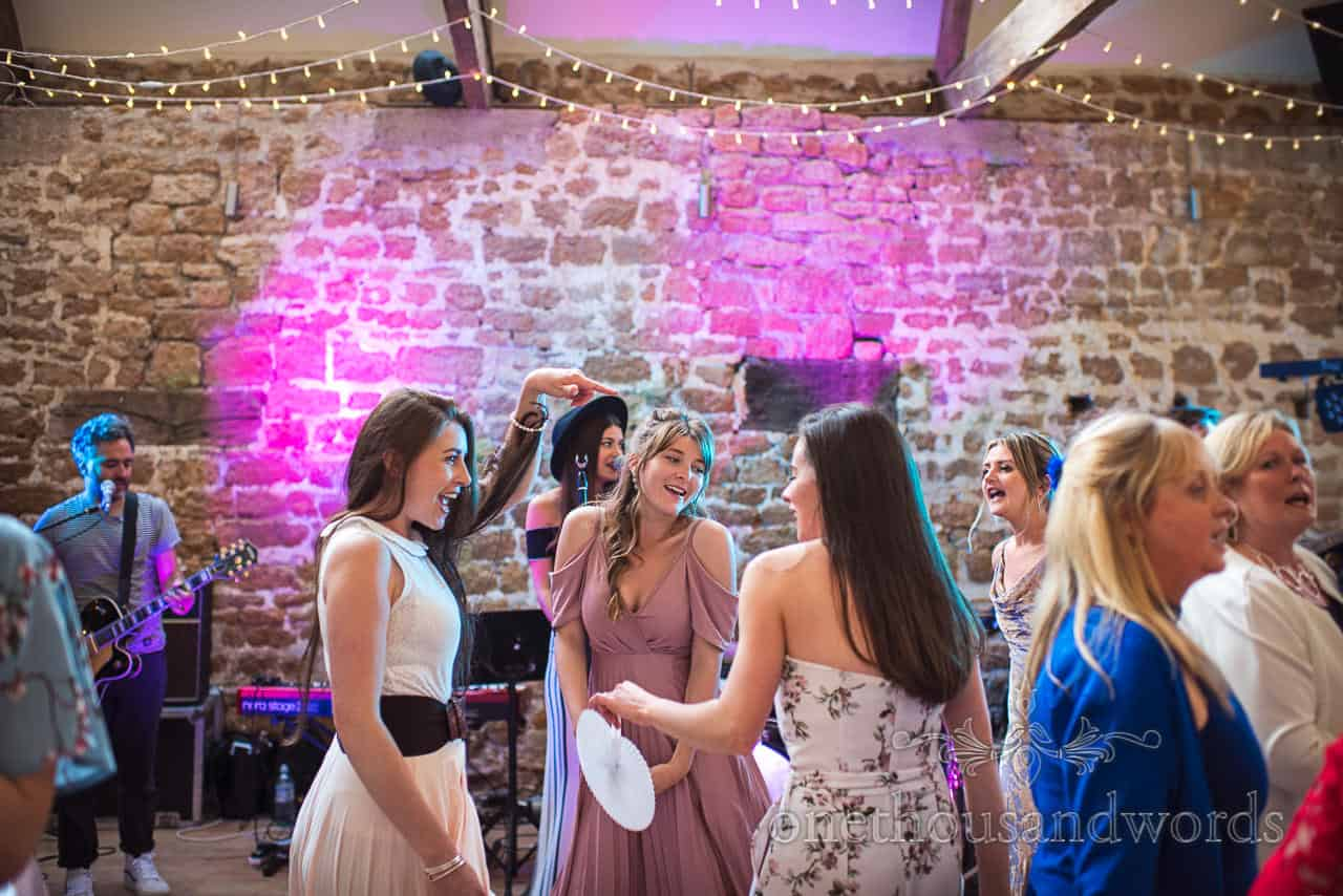 Female wedding guests dancing with fans at Tithe Barn Symondsbury wedding evening photograph in Dorset