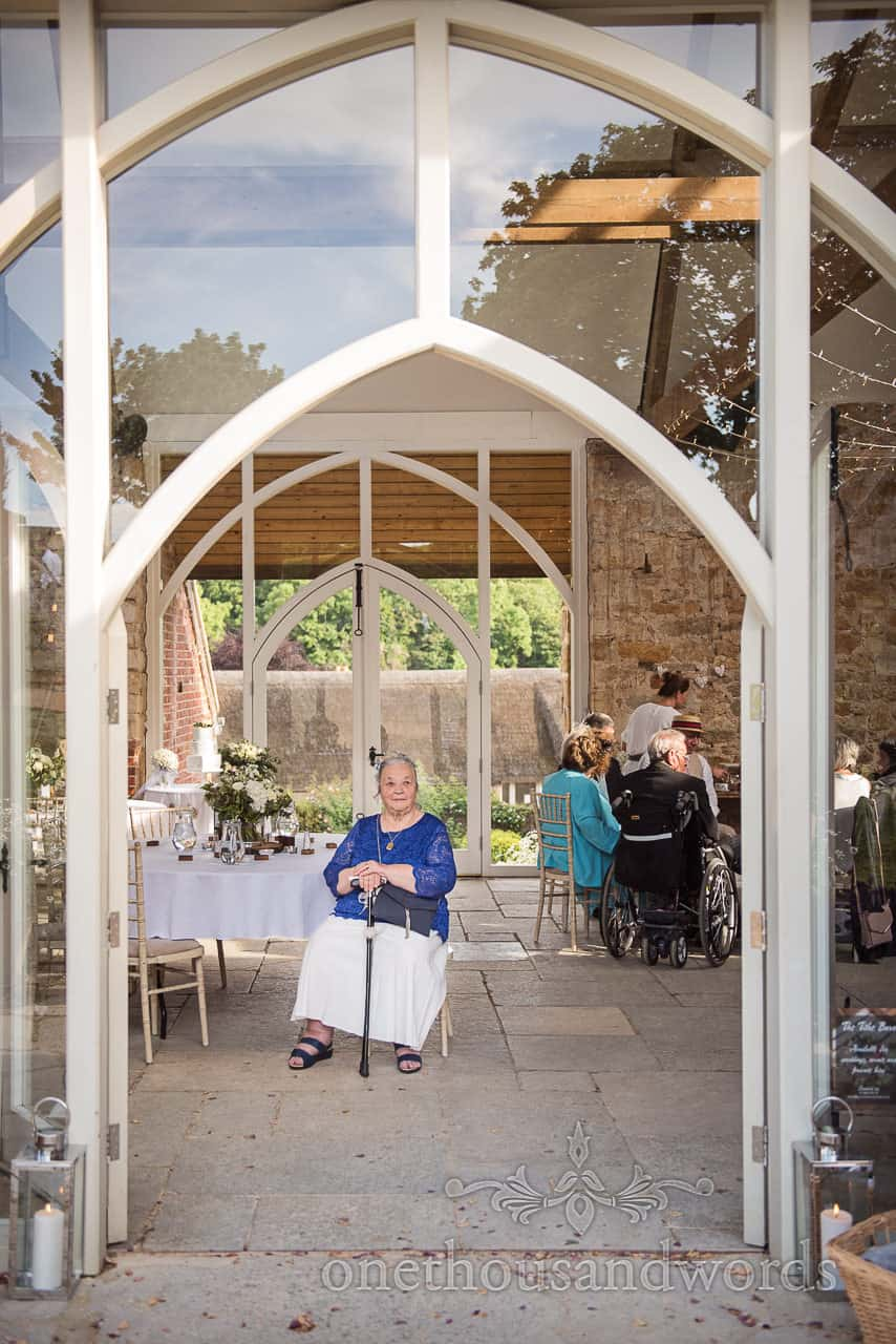 Bride's grandmother sits on chair waiting alone on stone floor in arched glass doorway at Tithe Barn Dorset Wedding venue
