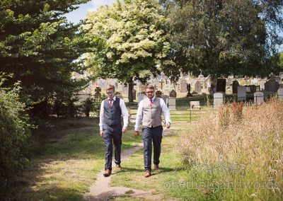 Groom and best man suited and booted wearing waistcoats in sunglasses walking through field on wedding morning