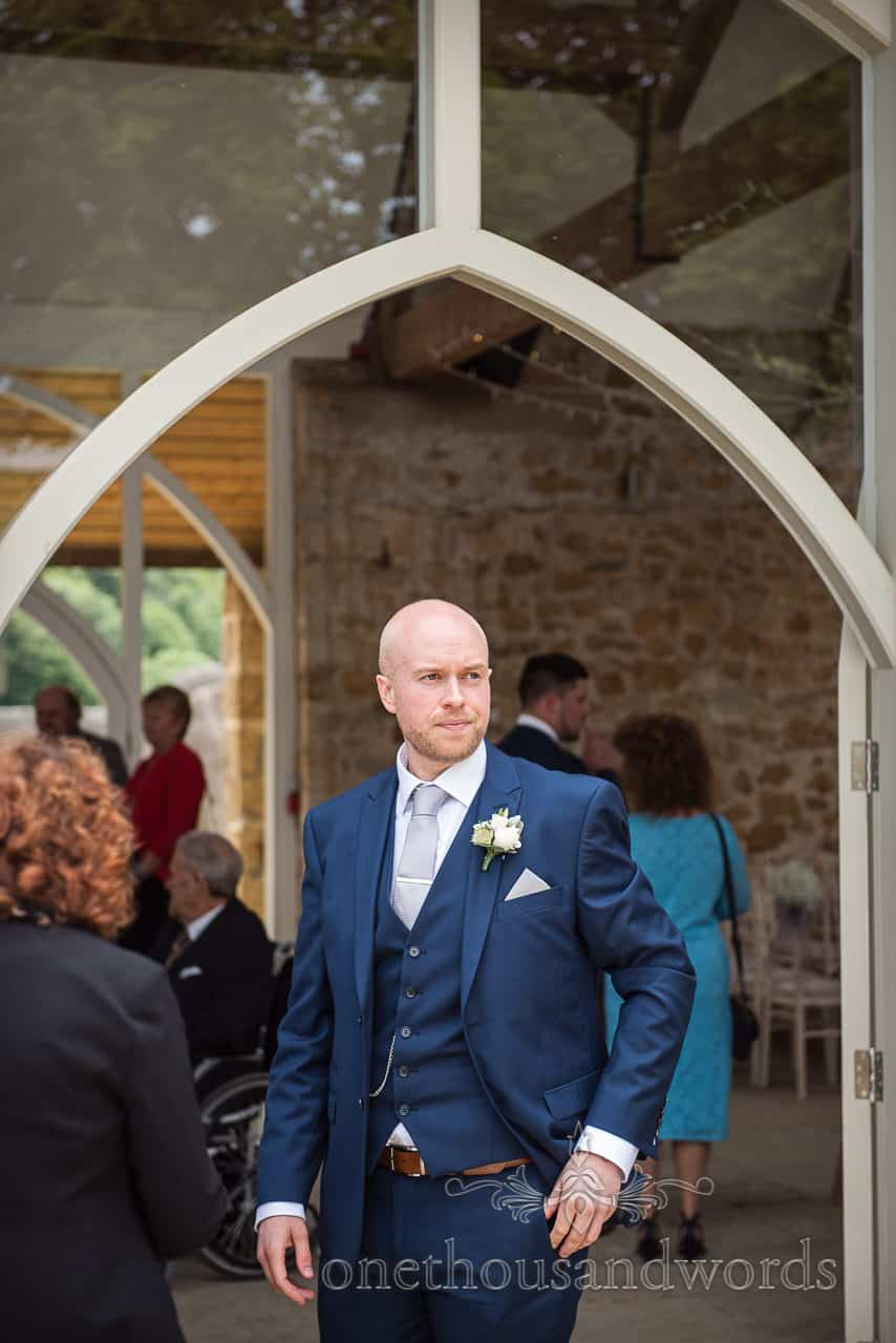 Groom in blue wedding suit outside arched doorway of barn venue nervously watches guests arriving for civil ceremony