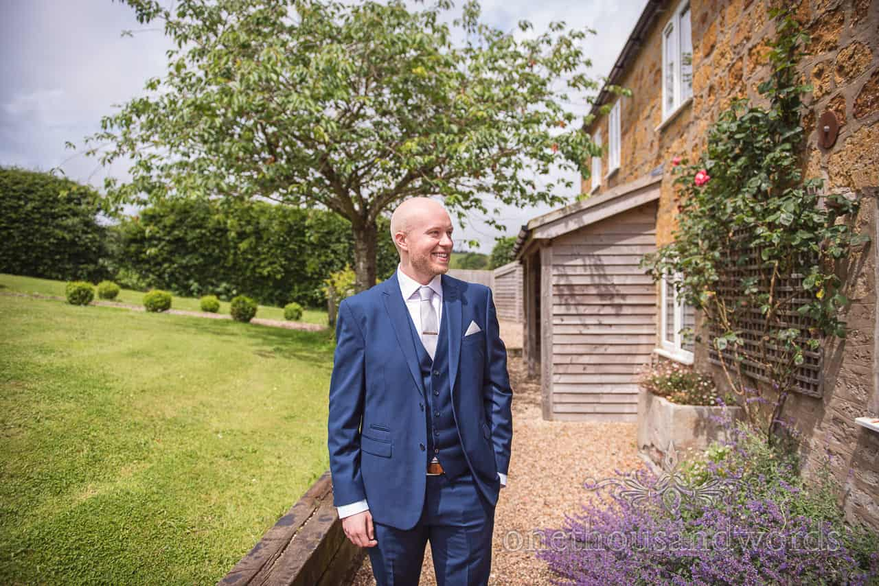 Happy groom in blue wedding suit outside Symondsbury Estate Crepe Cottage wedding morning venue gardens