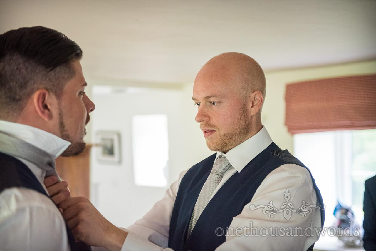 Portrait photograph of groom in blue waistcoat concentrating as he checks grooms man's tie on Dorset wedding morning