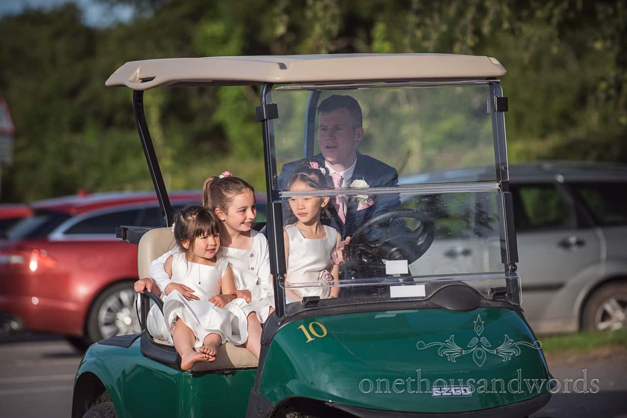 Groom drives a green golf cart through wedding venue car park with his three flower girl children in passenger seat