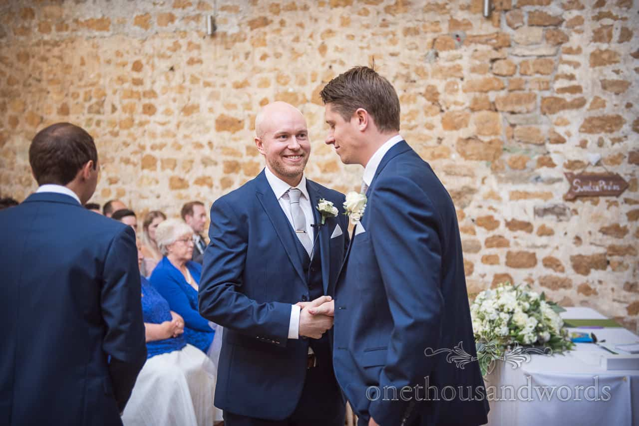 Happy groom and groomsmen shake hands whilst awaiting bridal party arrival at Tithe Barn Dorset wedding ceremony