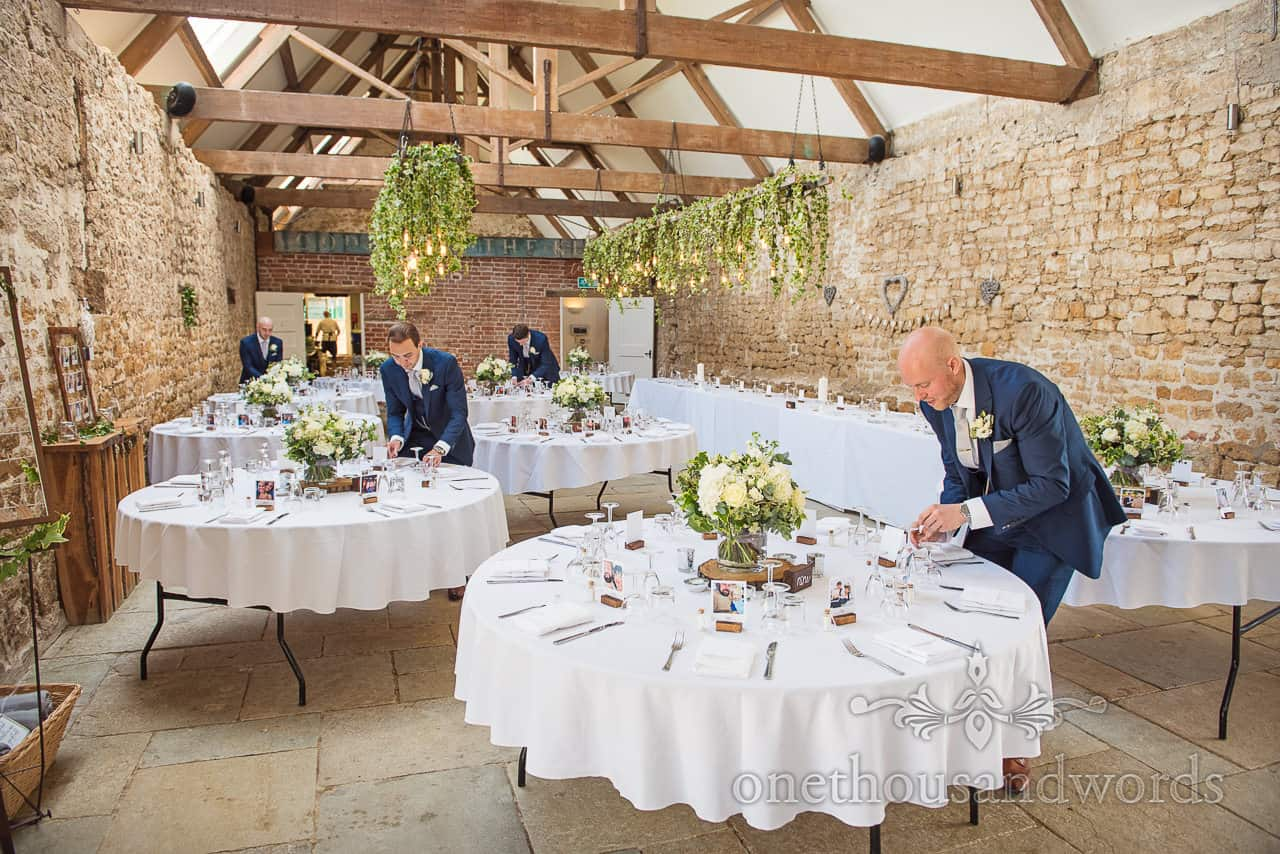 Groom and groomsmen in blue wedding suits check wedding table details at Tithe Barn wedding venue decorated interior in Dorset